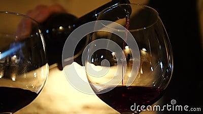 De wijn van de fles wordt gegoten in een glas stock footage
