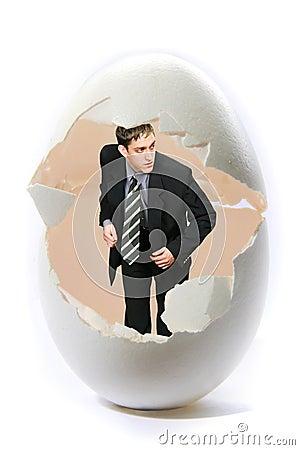 De zakenman kijkt uit groot ei