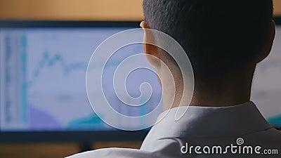 De zakenman werkt bij de computer, achteraanzicht Mannelijke makelaar bekijkt de statistieken van de aandelenverkoop op de markt stock videobeelden