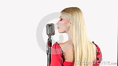De zanger in een rode kleding zingt in een retro microfoon Witte achtergrond Achter mening stock video