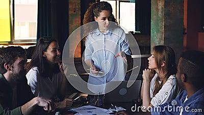 De zekere jonge vrouwenuitvoerende directeur spreekt aan multi-etnische groep medewerkers die vragen en het geven stellen stock videobeelden