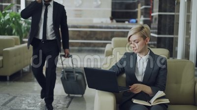 De zitting van de blondeonderneemster in leunstoel met blocnote en laptop computer terwijl zakenman die met bagage door lopen stock video