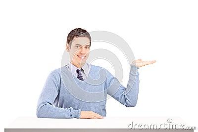 De zitting van de mens op een lijst en het gesturing met zijn hand