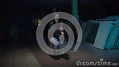 De zitting van de meisjesverslaafde op een stoel in een donkere ruimte die een injectie met drugs doen stock video