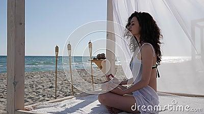De zomervakantie, diep ademmeisje die op kustoceaan, vrouw aan strand, vrouwen mediteren die yoga doen aan dijk, stock footage