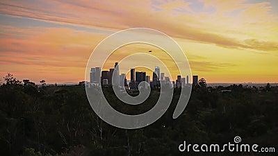 De zon valt op de horizon van Los Angeles aangezien een blimp hierboven de stad in vliegt stock videobeelden
