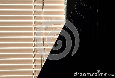De zonneblinden van het venster en lampschaduw
