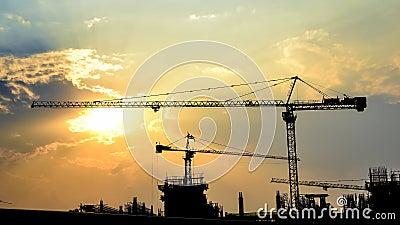 De zonsondergang van de tijdtijdspanne en silhouetkraan in bouwwerf