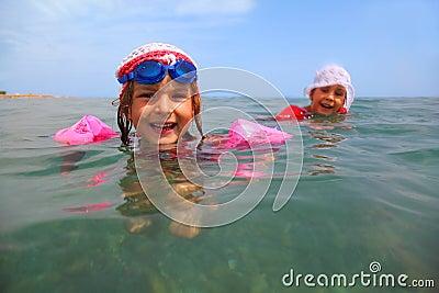 De zusters zwemmen in overzees. één meisje in glazen