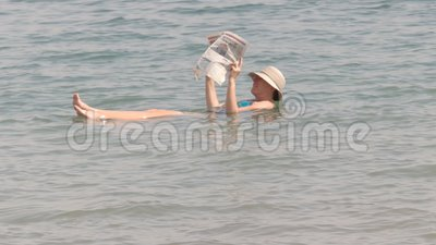 DEAD SEA, ISRAEL - SEPTEMBER, 22, 2016: woman reading a newspaper while floating in israel`s dead sea. DEAD SEA, ISRAEL - SEPTEMBER, 22, 2016: a woman reads a stock footage