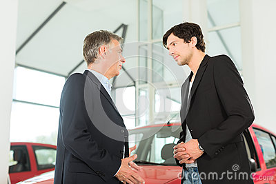 Dealer and young man with auto in car dealership