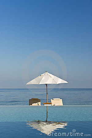 Free Deck Chair And Umbrella Next To Infinity Pool Royalty Free Stock Photography - 13540027