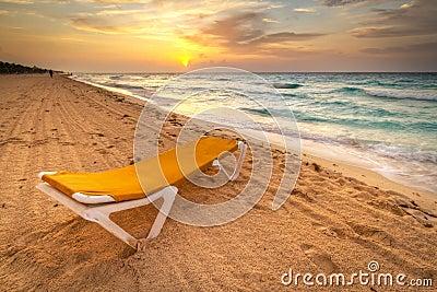 Deckchair amarillo en la salida del sol del Caribe