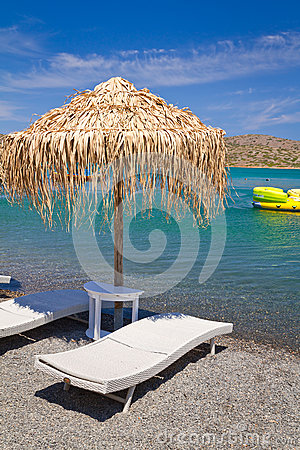 Deckchair under parasol at Aegean Sea