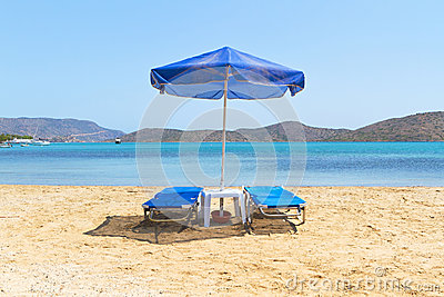 Deckchairs azuis sob o parasol