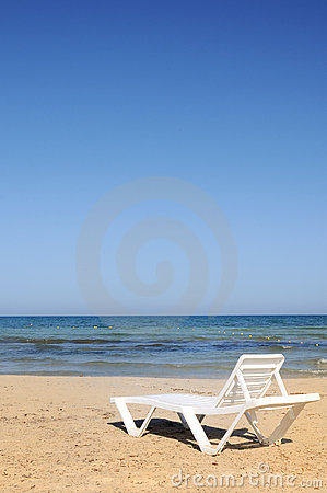 Deckchairs on the beach under blue sky