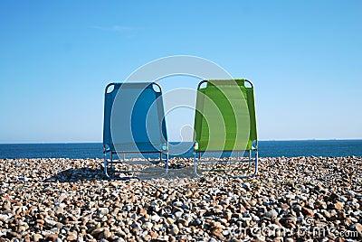 Deckchairs on pebble beach