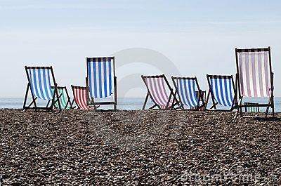 Deckchairs on shingle beach. UK