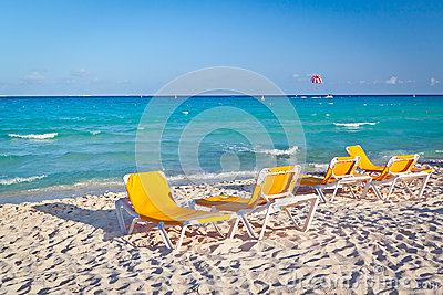 Deckchairs vacíos en la playa del Caribe