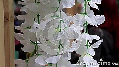 A decoração de flores falsas brancas e delicadas balançando no vento fecha em um festival de férias com pessoas desfocadas video estoque