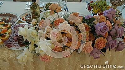 Decoración festiva de las flores frescas en la tabla, boda, MES lento, restaurante almacen de video
