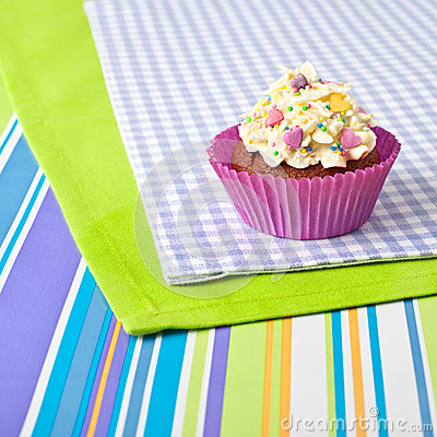 Decorated cupcake on stripy tablecloth