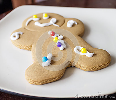 Decorated gingerbread man on white plate