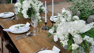 Decorating tables with bouquets of fresh flowers with candles and decor for a wedding or a party for a family feast. 4K stock video