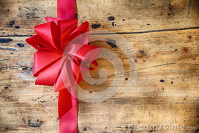Decorative red bow on rustic wood background