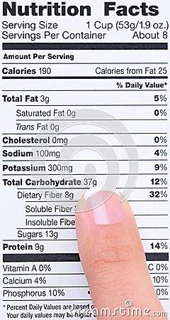 Dedo en escritura de la etiqueta de la nutrición