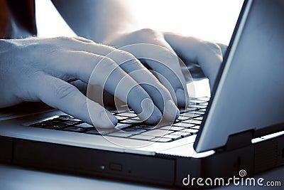 Dedos azules del tinte en el teclado