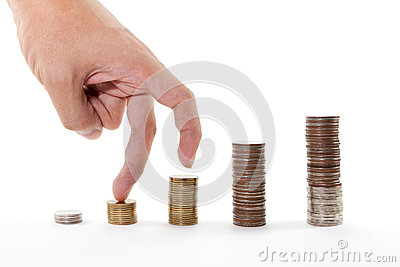 Dedos que caminan para arriba en pilas de monedas en el fondo blanco