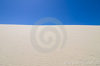 Deep blue sky against rippled sand dunes