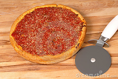 Deep dish pizza on a cutting board with cutter