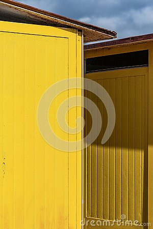 Deep yellow painted beach huts, on sunny but moody day. Blue sky, white clouds, seaside holiday architecture. Stock Photo