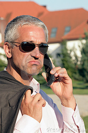 Dejected businessman using cell phone