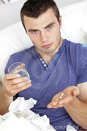 Dejected man holding pills and water on the sofa