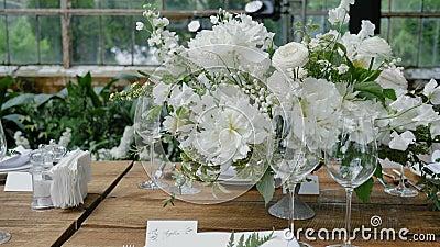 Dekorierte Holztische mit Bouquets aus frischen Blumen mit Kerzen und Dekor für eine Hochzeit oder eine Party für eine Familie stock video