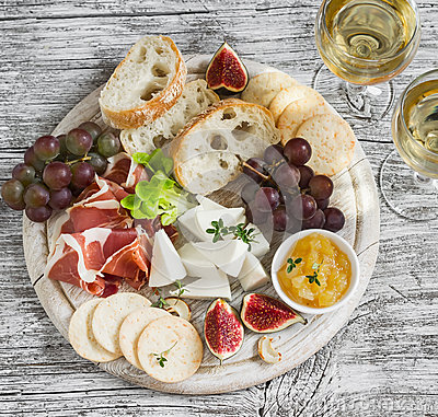 Free Delicious Appetizer To Wine - Ham, Cheese, Grapes, Crackers, Figs, Nuts, Jam, Served On A Light Wooden Board, And Two Glasses With Stock Images - 64679414