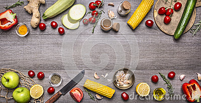 Delicious assortment of farm fresh vegetables with knife on grey wooden background , top view. Vegetarian ingredients for cooking. Stock Photo