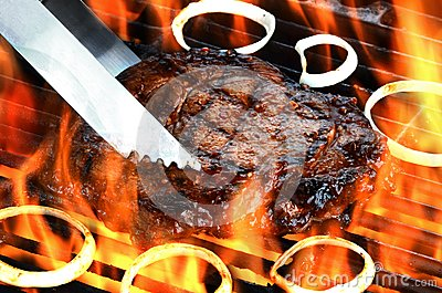 Delicious flame broiled rib eye steak on a flaming grill
