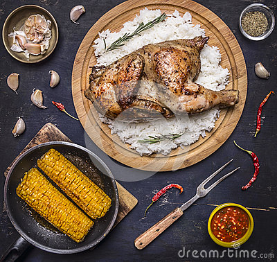 Free Delicious Fried Chicken With Rice On A Cutting Board, Fork For Meat, Spicy Sauce, Spices, Garlic And Corn In The Pan On Dark Blue Royalty Free Stock Photo - 62201165