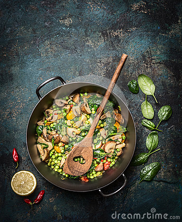 Free Delicious Steamed Healthy Vegetables In Cooking Pan With Ingredients And Wooden Spoon On Dark Rustic Background, Top View. Stock Photo - 65032920
