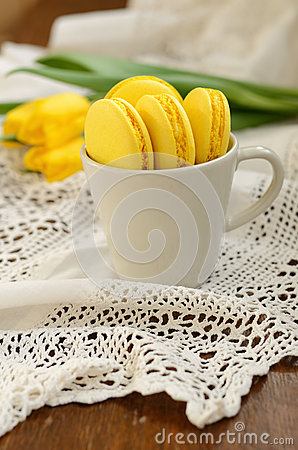 Delicious yellow macaroon and yellow tulips Stock Photo