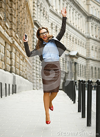 Free Delighted Business Woman Jumping For Joy While Talking On The Sm Royalty Free Stock Photo - 83179545