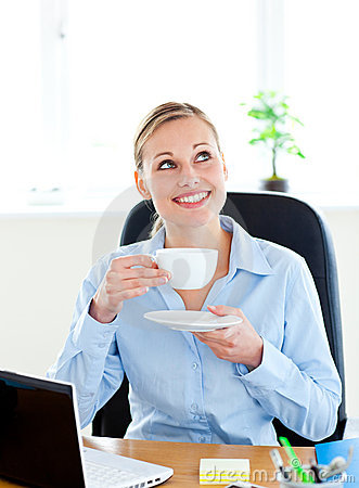 Delighted businesswoman drinking coffee at work