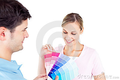 Delighted couple choosing color for a room