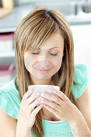 Delighted woman holding a cup of coffee