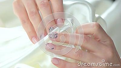 Delikatny kares biały jedwab żeńskimi rękami zdjęcie wideo