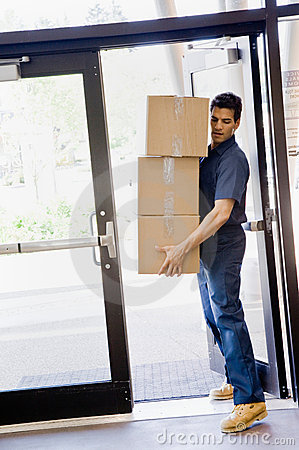 Delivery man carefully carrying stack of boxes